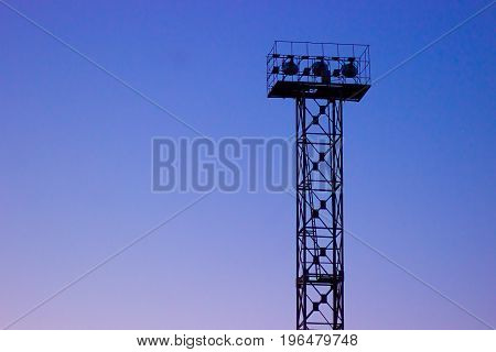 Stadium spot-light tower in a deep dawn evening