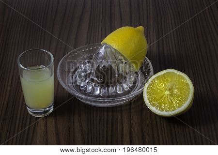Two halves of lemon and juice squeezed from one half in little glass on wood background