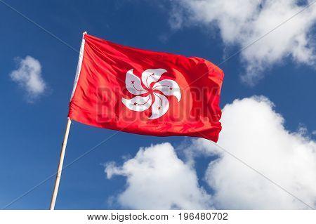 Hong Kong Flag Waving Over Blue Cloudy Sky