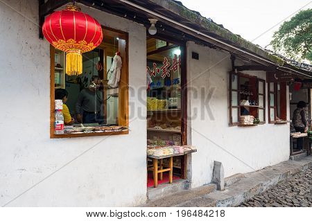 Suzhou, China - Nov 5, 2016: Passing a few food stores at the historic Zhouzhuang Water Town. A classical red lantern is hung outside one store.