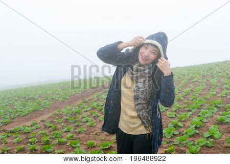 Walking woman in a cabbage farm cold with fog.