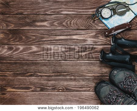 Hiking objects on a wooden background top view. Copy-space in left part of image.