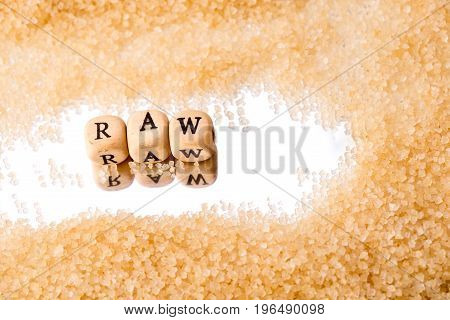Raw Sugar - Wooden Block Letters Reflected On Mirror Background Surrounded By Sugar Granules