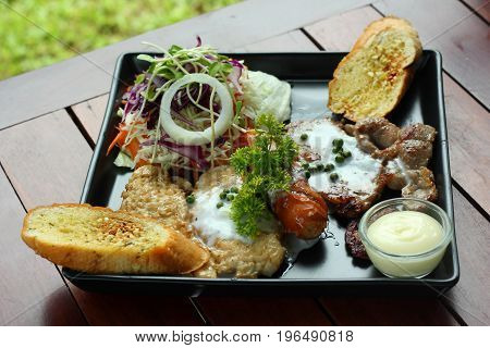 Mixed steaks recipe, grilled pork, sausage with garlic toast and vegetable salad.