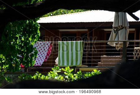 Colorful Towels Drying On A Wood Rail  At Deck Near Puako