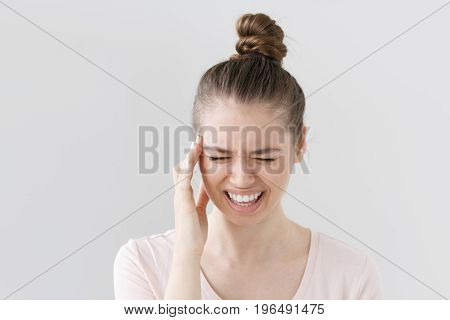 Horizontal Indoor Shot Of Beautiful Young Woman Isolated On Gray Background Squeezing Face Because O