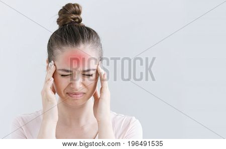 Portrait Of Female Isolated On Grey Background Suffering From Severe Headache, Pressing Fingers To T