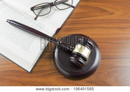Judge Gavel With Sound Board, Open Book And Glasses On A Wooden Desk, Top View From Above, Lawyers W
