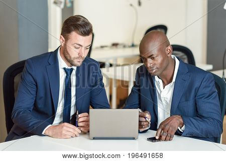 Black and caucasian businessmen looking at a laptop computer. Two men wearing blue suits working in an office with white furniture