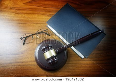 Judge Gavel With Sound Board, Blue Statute Book And Glasses On A Wooden Desk, Top View From Above, L