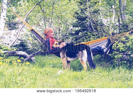 Man Traveler Is Relaxing In Hammock And Playing With His Dog
