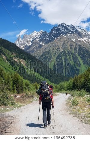 Man Adventurer With Big Dog Walks On The Road In A Mountain Gorge