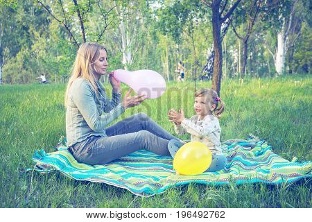 Mother With Her Amusing Daughter Inflates Colorful Balloons In Park