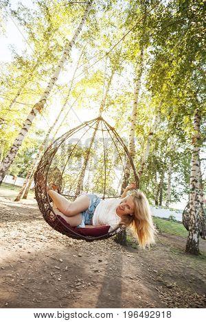 Joyful Young Woman Having Fun On A Hanging Chair