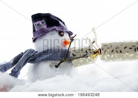 Cute snowman pulling a cracker wearing a hat and scarf in winter time at Christmas