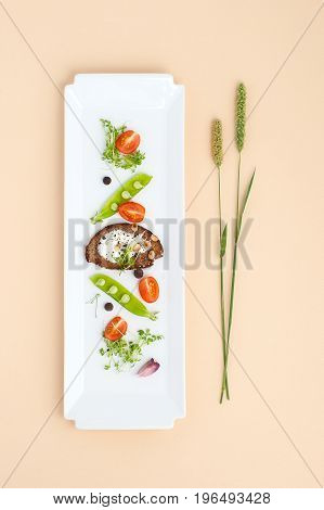 Salad Of Young Green Peas, Tomatoes And Croutons With Cream On A White Rectangular Plate..