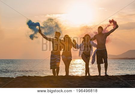 Group of happy people walkin on beautiful beach in summer sunset in their hands is smoke fontain