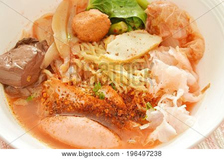 yellow noodles with shrimp and fish ball in red soup Chinese-language called Yong Tau Fu