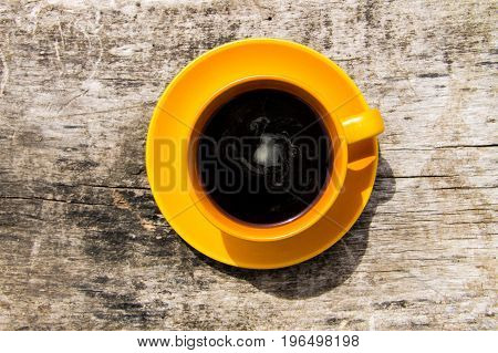 Cup of coffee on wooden table. Top view