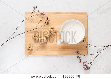 Dairy products. A cup of milk serve with almond candies on a rustic wooden table.