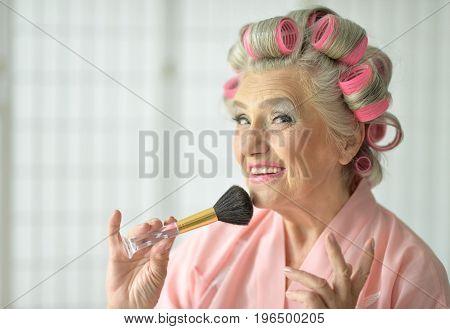 Close up portrait of senior woman in  bathrobe applying make up