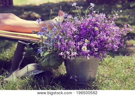 Large bouquet of wildflowers on a background of feet woman on a deck chair at summer day / summer vacation after working in the garden