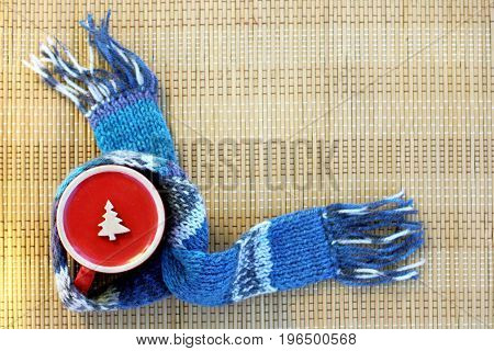 Inverted red cup with a Christmas tree symbol wrapped in a blue scarf / warming wishes from the other side