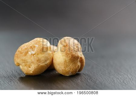 profiteroles on slate background closeup, shallow focus