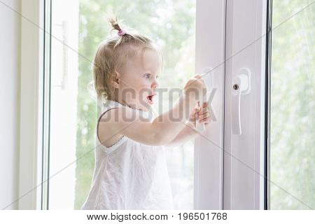 Small child opens window with key. girl is standing on window sill by window. Window with lock.