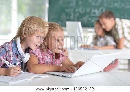 Cute little brother and sister sitting at table and using laptop