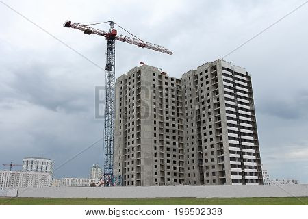 Construction of an apartment building with a crane. Construction site with a crane.