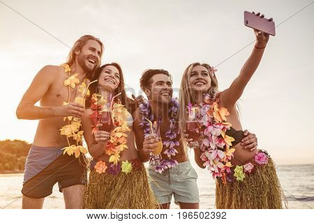 Group of young attractive friends are having fun on beach smiling and making selfie. Party in Hawaiian style.