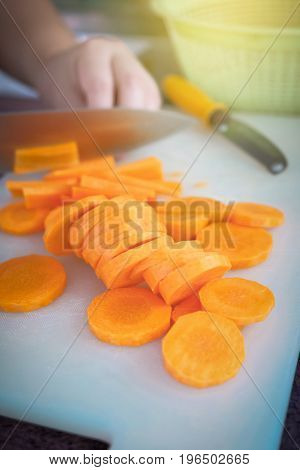 Slicing carrots by knife holding in woman hand for cooking