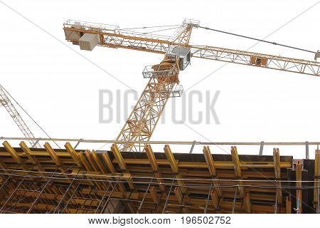 Construction crane on construction site isolated on white background. Construction crane and monolithic concrete walls in formwork close-up. Concept of construction.