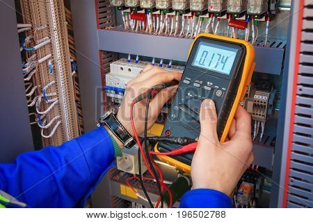Electrical Engineer adjusts electrical equipment with a multimeter in his hand closeup. Professional electrician in electric automation cabinet