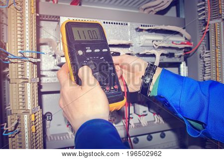 Hands of electrician close-up with multimeter. engineer measures voltage and tests electrical control cabinet of industrial equipment.