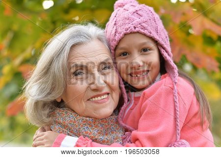 Happy grandmother and granddaughter in autumnal park