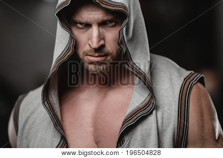 Muscular Handsome Athletic Bodybuilder Fitness Model Posing After Exercises In Gym On Diet With Hood