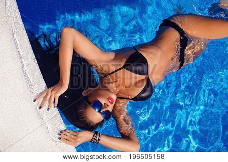 Beautiful tanned young woman with perfect body wearing black bikini and sunglasses relaxing in swimming pool. outdoor shot. copy space.