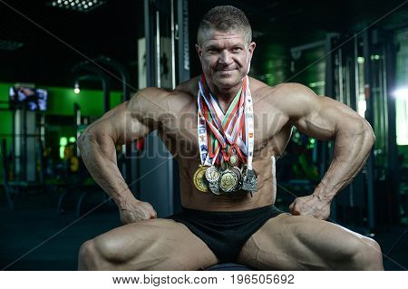 Brutal Strong Bodybuilder With Medals Man Pumping Up Muscles And Train Gym
