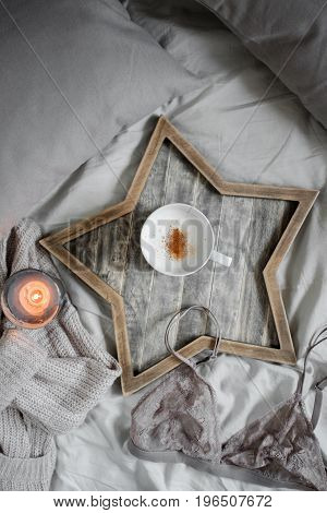 A cup of coffee and a candle in a Scandinavian wooden tray in a cozy bed with a blanket.  top view.