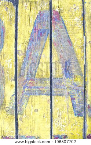 Painted letter A on yellow woden desk. Fragmet of text.