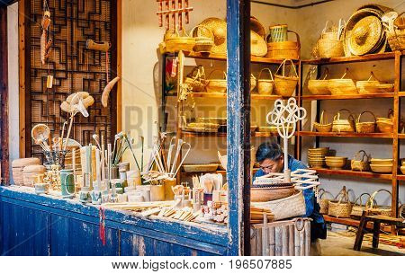 Suzhou, China - Nov 5, 2016: Man sitting behind his store quietly making handicrafts for sale at the historic Zhouzhuang Water Town.