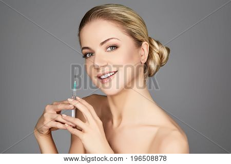 beautiful happy young woman holding syringe with collagen treatment injection. beauty shot on grey background. copy space.