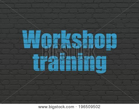 Education concept: Painted blue text Workshop Training on Black Brick wall background