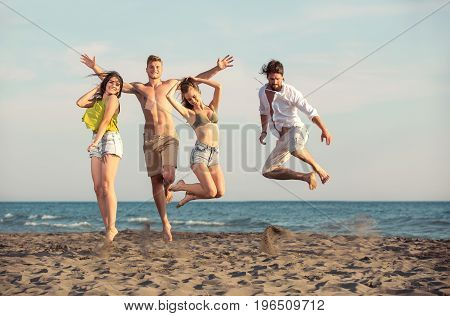 Group of friends together on the beach having fun. Happy young people jumping on the beach.