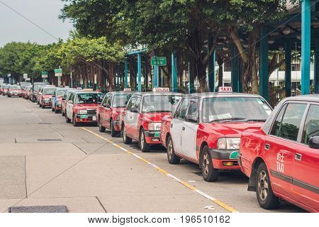 A Fleet Of Hong Kong Taxis Waiting At A Taxi Stand. Hong Kong Taxis Are Easily Recognizable By Their