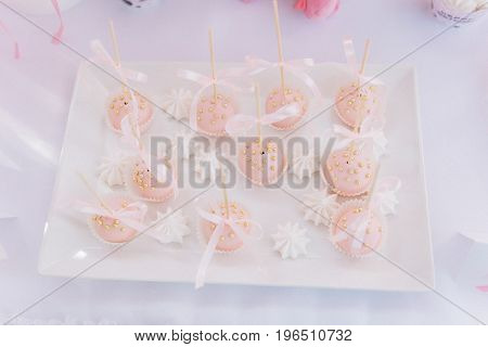 Pink cupcakes with the golden drops and ribbons on the white plate