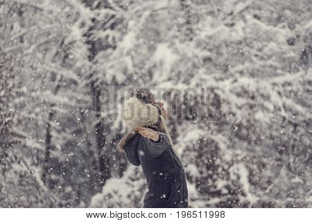 Retro effect faded and toned image of a woman celebrating winter standing outdoors in falling snow with her arms outspread.