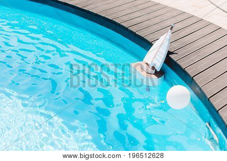 Wooden toy boat in the swimming pool with clear water